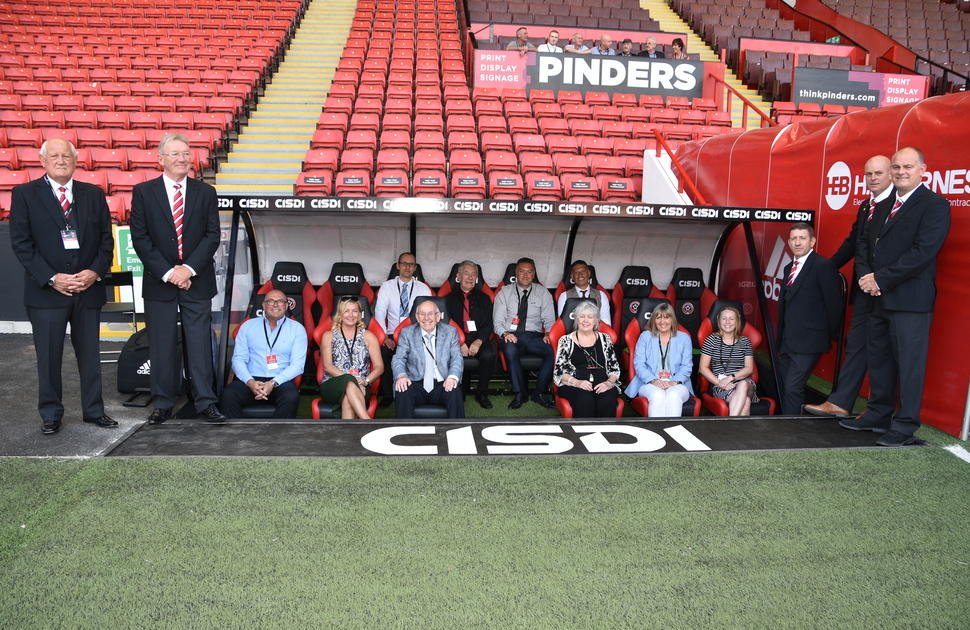 MEPS Staff in the dugout at Bramall Lane, surrounded by Sheffield United legends